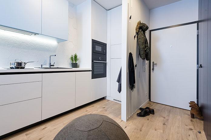 Drzwi wejściowe do mieszkania w bloku – widok na przedpokój i aneks kuchenny